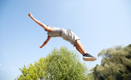 levitation: fitness, sport, parkour and people concept - young man jumping in summer park Stock Photo