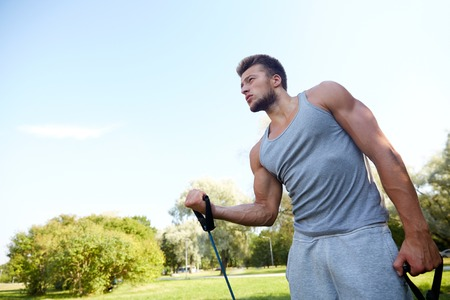 expander: fitness, sport, exercising, training and lifestyle concept - young man exercising with expander in summer park