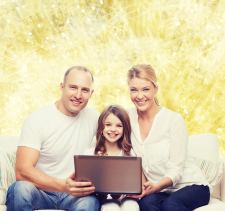 kids laptop: family, childhood, holidays, technology and people concept - smiling family with laptop computer over golden lights background Stock Photo