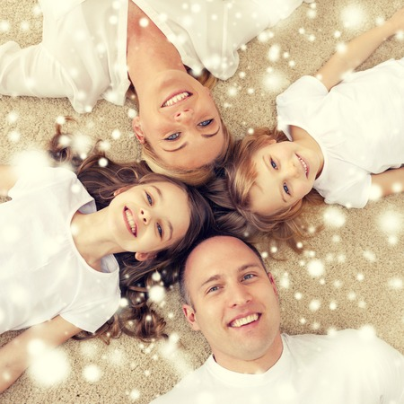 young woman face: family, children and home concept - smiling family with and two little girls lying in circle on floor at home