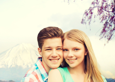 teenage girl: people, vacation, love and travel concept - smiling couple hugging over japan mountains background Stock Photo