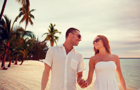 lovers holding hands: love, people, travel, summer and relations concept - smiling couple wearing sunglasses walking outdoors over tropical beach background