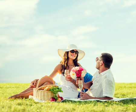 couple dating: love, dating, people and holidays concept - smiling couple drinking champagne on picnic outdoors Stock Photo