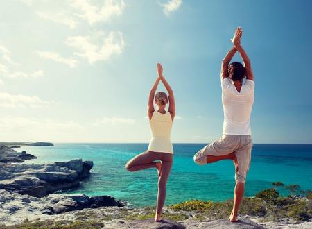 motion: fitness, sport, och livsstilskoncept - par gör yogaövningar på stranden från baksidan