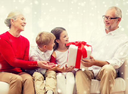 familie, vakantie, generatie, kerst en mensen concept - lachende grootouders en kleinkinderen met cadeau doos zitten op de bank thuis Stockfoto