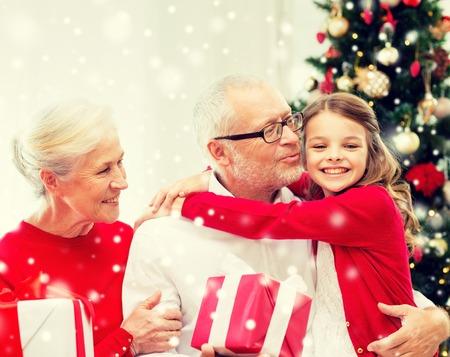 rodina, dovolená, generace, vánoční a lidé koncept - usmívající se prarodiče a vnučka s dárkové krabičky sedí na gauči doma