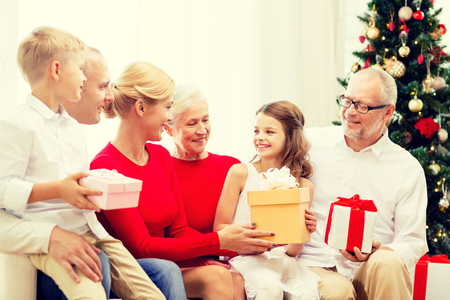 three presents: family, holidays, generation, christmas and people concept - smiling family with gift boxes sitting on couch at home