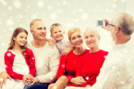 mama e hija: family, holidays, generation, christmas and people concept - smiling family with camera photographing and sitting on couch at home
