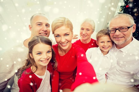 take a smile: family, holidays, generation, christmas and people concept - smiling family with camera or smartphone taking selfie at home