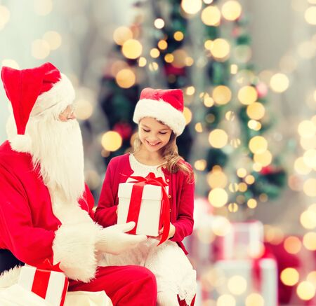 young tree: holidays, childhood and people concept - smiling little girl with santa claus and gifts over christmas tree lights lights background