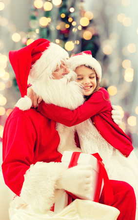 christmas party: holidays, celebration, childhood and people concept - smiling little girl hugging with santa claus over christmas tree lights background Stock Photo