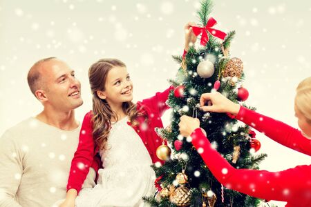 decorating: family, holidays, generation and people concept - smiling family decorating christmas tree at home