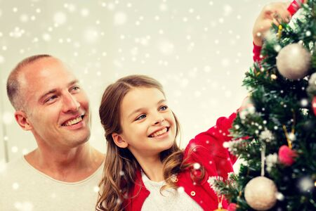 happy holidays: family, holidays, generation and people concept - smiling girl with father decorating christmas tree at home