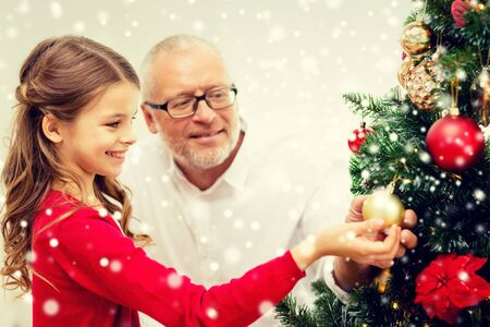 decorating: family, holidays, generation and people concept - smiling girl with grandfather decorating christmas tree at home