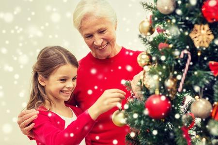 abuelos: concepto de familia, las vacaciones, la generación y la gente - sonriente niña con la abuela decorar el árbol de Navidad en casa