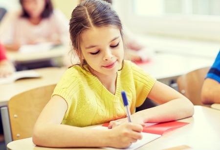 niño escuela: educación, escuela primaria, el aprendizaje y el concepto de la gente - grupo de niños de la escuela con lápices y cuadernos de escritura de prueba en el aula Foto de archivo