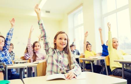 学校のグループがノートブック教室に座っていると、手を上げると子供教育、小学校、学習、人々 のコンセプト-