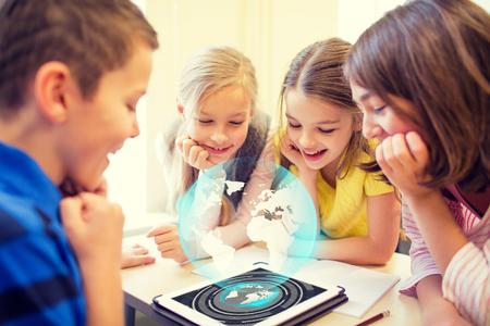niños felices: educación, escuela primaria, el aprendizaje, la tecnología y el concepto de la gente - grupo de niños de la escuela en busca de la pantalla del ordenador Tablet PC con el globo holograma en ruptura en el aula