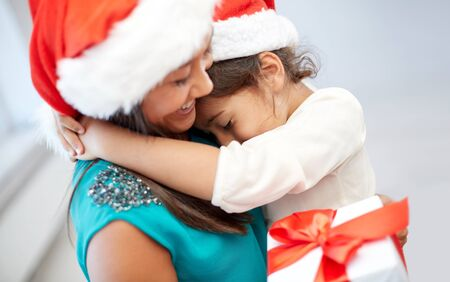 asian child: christmas, holidays, family, childhood and people concept - happy mother and little girl in santa hats cuddling at home