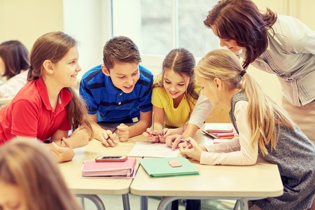 maestro: educaci�n, escuela primaria, el aprendizaje y el concepto de la gente - Profesor de ayudar a ni�os de la escuela de escritura de prueba en el aula Foto de archivo