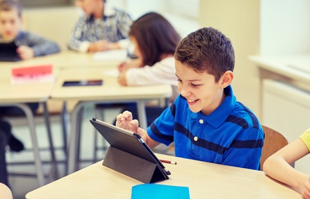 education, elementary school, learning, technology and people concept - little schoolboy with tablet pc computer on break in classroom