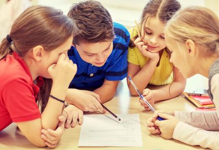 salon de clases: educaci�n, escuela primaria, el aprendizaje y el concepto de la gente - grupo de ni�os de la escuela con l�pices y papeles de escritura en el aula Foto de archivo