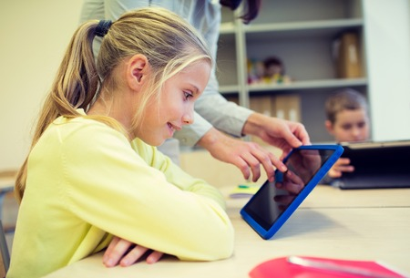 elementary: education, elementary school, learning, technology and people concept - little girl with teacher and tablet pc computer in classroom Stock Photo