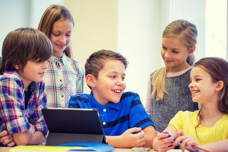 niños estudiando: educación, escuela primaria, el aprendizaje, la tecnología y el concepto de la gente - grupo de niños de la escuela con la computadora Tablet PC que se divierte en descanso en el aula