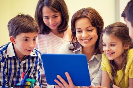 technology: educación, escuela primaria, el aprendizaje, la tecnología y el concepto de la gente - grupo de niños de la escuela con el maestro mira al ordenador Tablet PC en el aula Foto de archivo