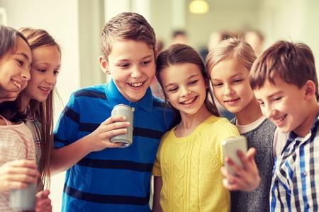 onderwijs, basisschool, drankjes, kinderen en mensen concept - groep schoolkinderen met smartphone en blikjes frisdrank nemen selfie in gang