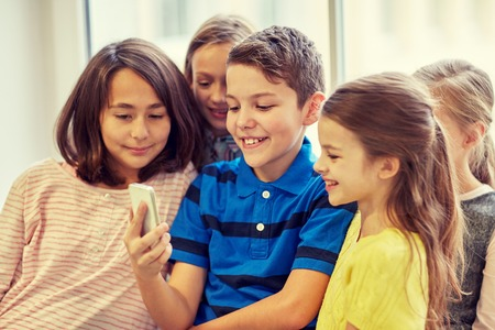 asian preteen: education, elementary school, drinks, children and people concept - group of school kids taking selfie with smartphone in corridor Stock Photo