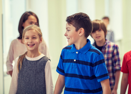 going: education, elementary school, drinks, children and people concept - group of smiling school kids walking in corridor