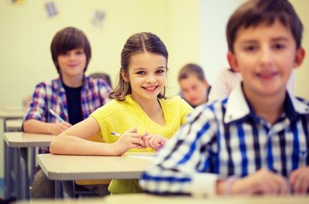 onderwijs, basisschool, leren en mensen concept - groep schoolkinderen met pennen zitten in de klas Stockfoto