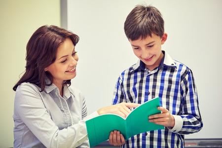 preguntando: educación, escuela primaria, el aprendizaje, la exploración y la gente concepto - muchacho de escuela con el cuaderno y el profesor en el aula Foto de archivo