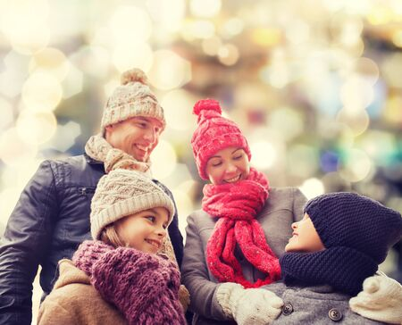 christmas woman: family, childhood, season, holidays and people concept - happy family in winter clothes over lights background Stock Photo