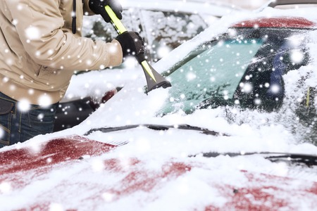 winter weather: transportation, winter, weather, people and vehicle concept - closeup of man cleaning snow from car windshield with brush