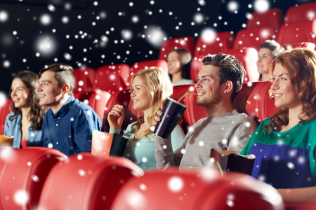 el cine, el entretenimiento y la gente concepto - amigos felices con las bebidas de palomitas de maíz y limonada miran película en el teatro con copos de nieve