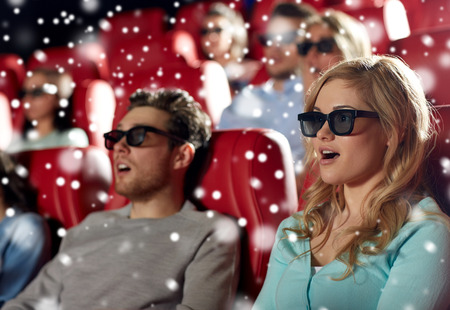 thriller: cinema, technology, entertainment and people concept - young woman in 3d glasses watching horror or thriller movie with friends in theater with snowflakes Stock Photo