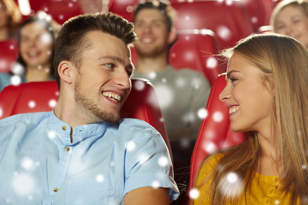 winter theater: cinema, entertainment and people concept - happy friends or couple watching movie and talking in theater with snowflakes Stock Photo