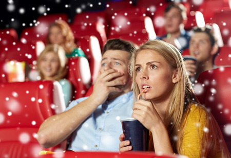christmas movies: cinema, entertainment and people concept - terrified couple drinking soda and watching horror, drama or thriller movie in theater with snowflakes