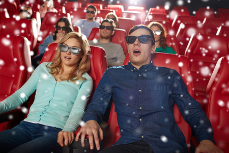 asustado: el cine, la tecnología, el entretenimiento y la gente concepto - amigos asustados o pareja con gafas 3D viendo el horror o el thriller en el teatro con copos de nieve
