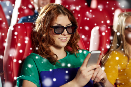 christmas movies: cinema, technology, entertainment and people concept - happy woman in 3d glasses reading message on smartphone in movie theater with friends over snowflakes