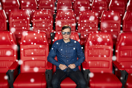 christmas movies: cinema, technology, entertainment and people concept - young man in 3d glasses watching movie alone in empty theater auditorium with snowflakes