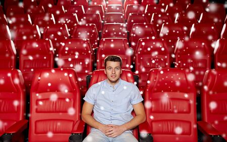 empty of people: cinema, entertainment and people concept - happy young man watching movie alone in empty theater auditorium with snowflakes Stock Photo
