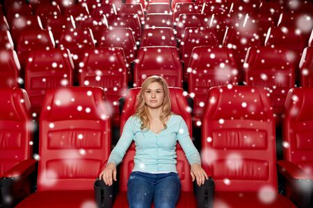empty of people: cinema, entertainment and people concept - young woman watching movie alone in empty theater auditorium with snowflakes