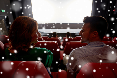 winter theater: cinema, entertainment and people concept - happy friends or couple watching movie in theater on last row and talking from back over snowflakes