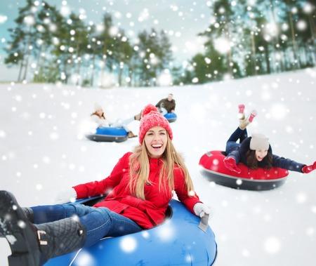 겨울, 레저, 스포츠, 우정과 사람들 개념 - 행복 친구의 그룹은 눈 튜브에 아래로 슬라이딩