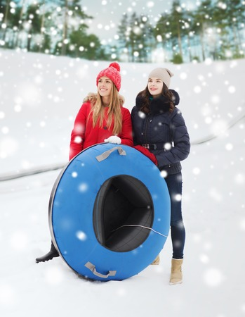 tubes: winter, leisure, sport, friendship and people concept - happy girl friends with snow tubes outdoors