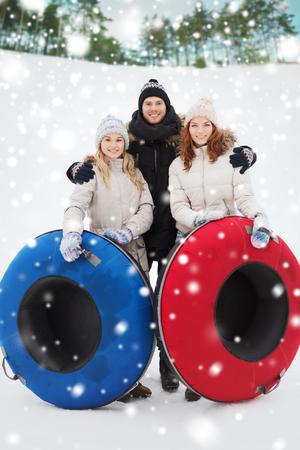 jovenes felices: invierno, el ocio, el deporte, la amistad y el concepto de la gente - grupo de amigos sonriendo con tubos de nieve al aire libre