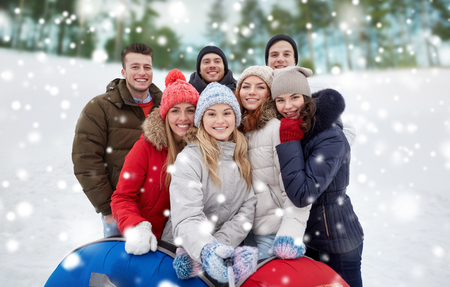 young men: winter, leisure, friendship, technology and people concept - group of smiling young men and women with snow tubes taking picture with smartphone selfie stick outdoors